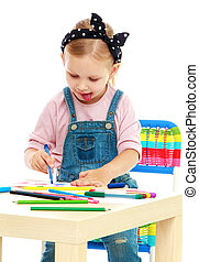 Funny little girl draws with pens sticking out his tongue-...