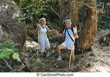 elderly couple walking in the forest - Active elderly couple...