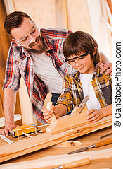 Teaching his son all about carpentry. Happy young male...