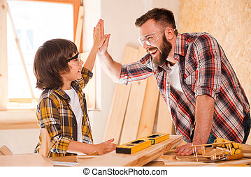 We did it Cheerful young male carpenter and his son giving...