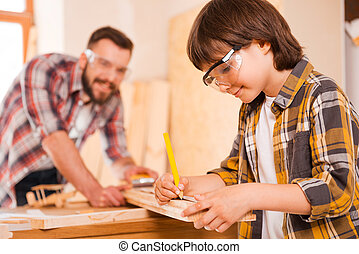 Hardworking is a key to success. Smiling little boymaking measurements on the wooden plank while working with his father in workshop