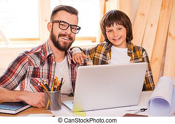 Father and son working together. Cheerful young man working...