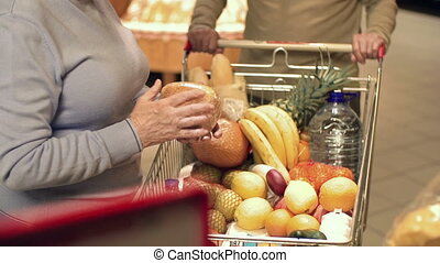 Shopping at the Supermarket - Tilt up of elderly couple...