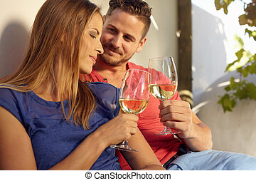 Young couple celebrating with white wine together, outdoors...