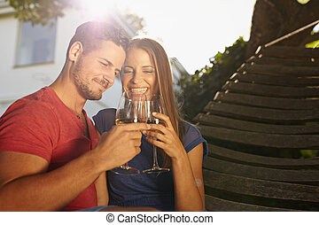 Couple celebrating with wine in backyard - Outdoor shot of...