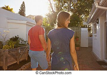 Young couple walking towards their house - Rear view of...