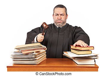 Angry male judge in a courtroom striking the gavel and...