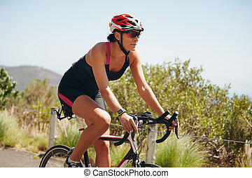 Young woman triathlon athlete cycling on country road. Woman...
