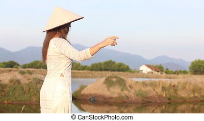 blonde girl in vietnamese costume and hat poses near pond -...