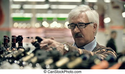 Wine Selection - Head shot of a man choosing wine in the...