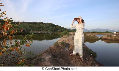 blonde girl in vietnamese costume and hat poses between...