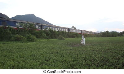 blonde girl in vietnamese poses in valley against train -...