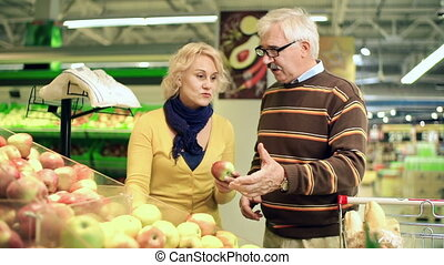At the Greengrocery - Close up of married couple picking...