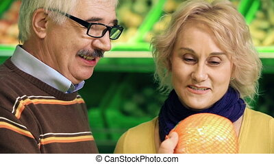 Shopping for Fruits - Close up of couple examining...
