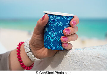 Blue cup of coffee in a female hand on a beach background...