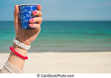 Blue cup of coffee with an ornament in the left female hand...