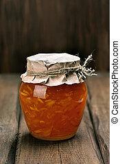 Orange homemade jam marmelade in glass jar on wooden table
