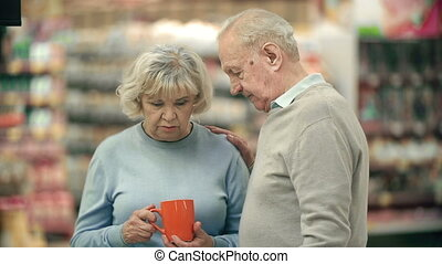 Right Choice - Close up of senior couple choosing a cup to...