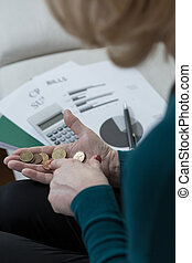 Woman counting coins - Woman counting money to pay her bills