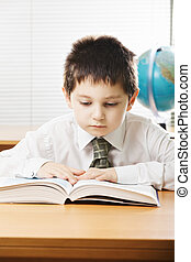Caucasian boy reading book at the desk in classroom
