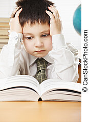 Boy having hard reading - Caucasian boy sitting at the desk...