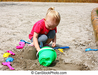 Little girl playing in the sand