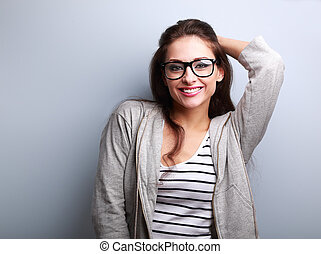Happy casual young woman in glasses on blue background -...