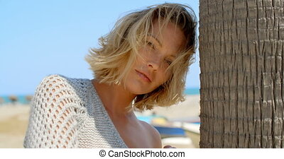 Woman with Wind Swept Hair Next to Tree on Beach - Coy...