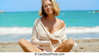 Blond Woman Sitting Crossed Legged on Beach - Portrait of...