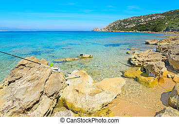 fishing rod on the rocks in Capo Testa, Sardinia