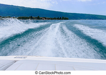 waves behind a motorboat on the lake