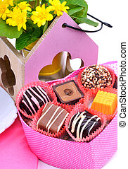 chocolate sweets in gift boxes, yellow wildflowers