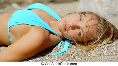 Blond Woman Suntanning on Beach with Eyes Closed - Smiling...