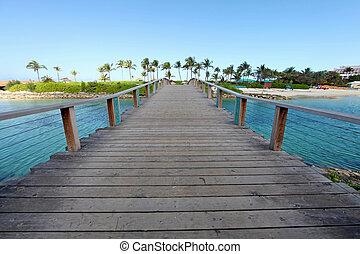 Bridge - A wooden bridge over water going over to a beach