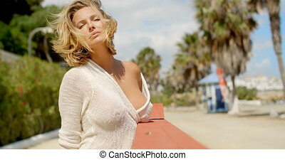 Blond Woman with Hand in Hair Standing on Beach