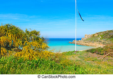Flagpole by the shore in Rena Bianca, Sardinia