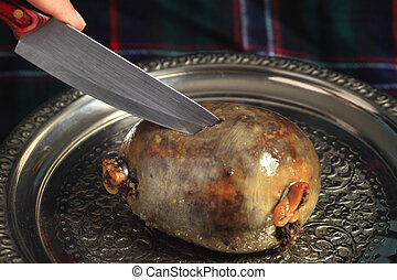 Cutting the haggis - A haggis on a silver tray being cut, a...