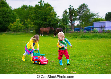 Kids playing on a farm - Family on a horse farm in summer....