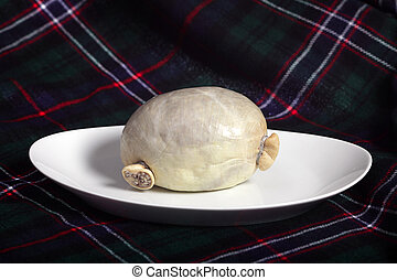 Haggis with tartan - A traditional raw Scottish haggis, in a...