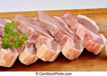 some raw organic pork chop and parsley