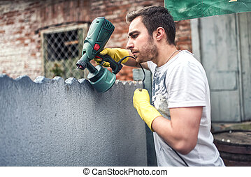 Professional construction worker painting walls at house renovation. Exterior building renovation with spray gun painter