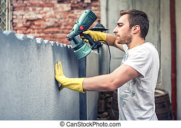 Man using protective gloves painting a grey wall with spray paint gun. Young worker renovating house