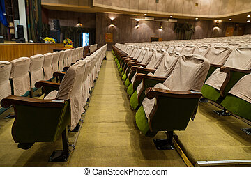 Rows of Empty Seats in Well Lit Theater