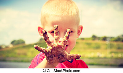 Child playing outdoor showing dirty muddy hands. - Child...