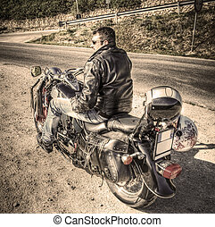 side view of a biker in sepia tone - biker on a classic...