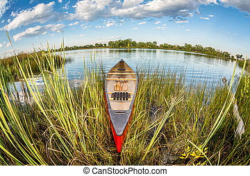 canoe in fish eye lens perspectrive - red canoe on a lake...