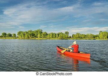 afternoon canoe paddling on lake - male paddler paddling a...