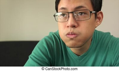 Bored Asian Man Watching TV Changes Channel With Remote -...