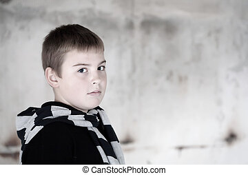 Boy against grunge background lit with flash overexposed...