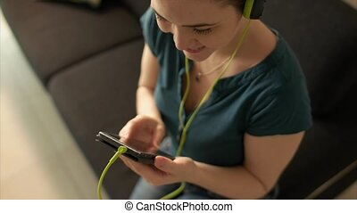 Woman With Mobile Phone Listens Music Podcast Earphones -...